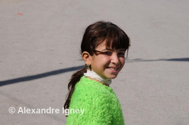 Little Uzbek smiling girl in green sweater