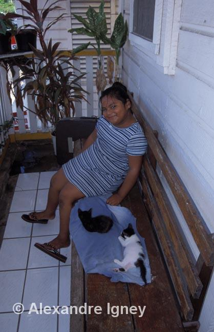 girl and cats on a bench in Belize City
